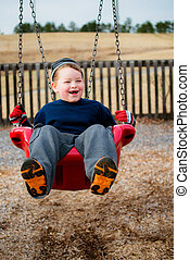 Happy child laughing while swinging