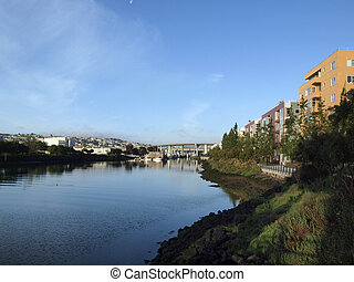 Shoreline of Mission Creek lined with buildings, house boats and highway going over creek in the distance in San Francisco, California