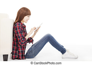 young woman using tablet and sitting on the floor