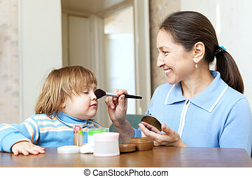 grandmother putting facepowder on face of girl - Smiling...
