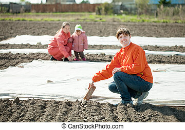 family covers soil a polyethylene film - Happy family covers...