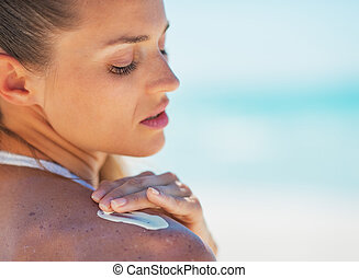 Portrait of young woman applying sun screen creme