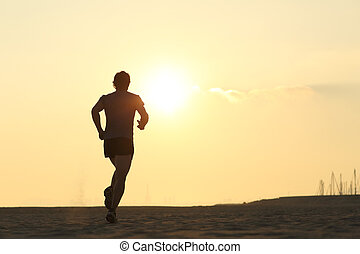Backlight of a jogger running on the beach with the sun...