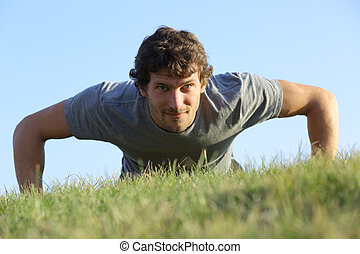 Close up of a man doing pushups on the grass with the...