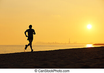 Jogger silhouette running on the beach at sunset with the...