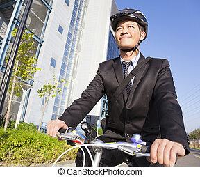 smiling businessman riding a bicycle to workplace