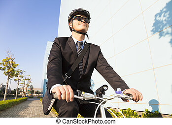 businessman riding a bicycle to workplace for protecting...