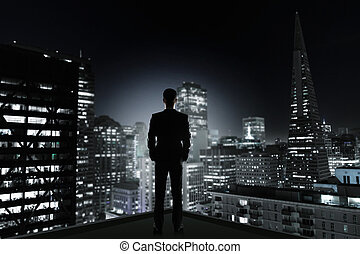 man and night city - man in office looking to night city