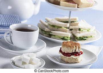 English Tea Time - Cup of tea with sugar cubes and scones,...