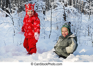 Beautiful boy and girl in winter snow-covered forest -...