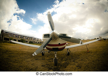 foto of an small airplane on green grass and sunset...