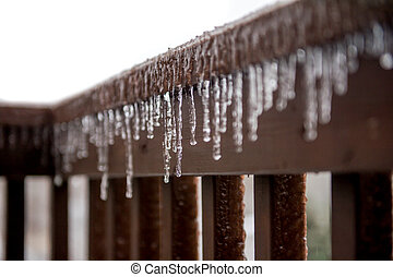 Icicles hanging down from railing - Several icicles hanging...