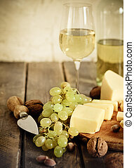 Bottles and glass of white wine, cheese, nuts and grapes on...