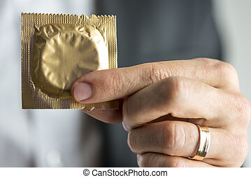 Cheating - Closeup of married man hand holding a condom....