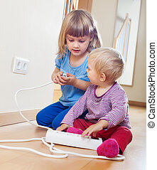 Two children playing with electricity at home