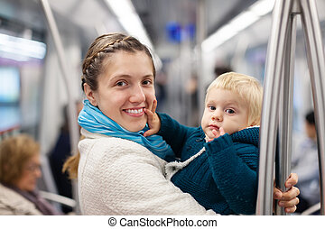 young mother with baby in subway train at metro