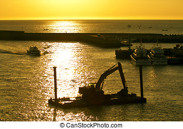 excavator machine construct on sea under twilight - A large...