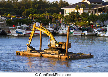 excavator machine construct on sea - A large yellow...