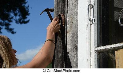 girl hammer horse shoe - Closeup of blond girl woman hammer...
