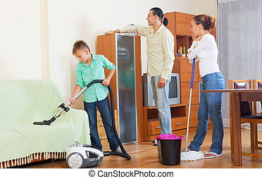 House cleaning - Middle-aged couple with teenage son doing...
