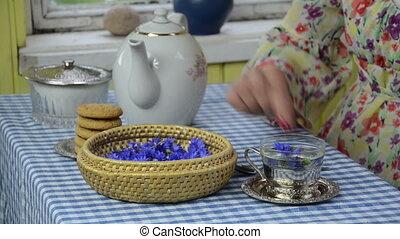 hand cornflower tea - Closeup of woman hand put cornflower...