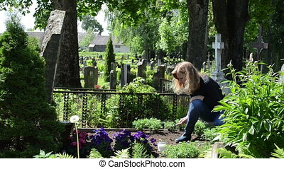 woman loosen grave ground - woman girl work on father...
