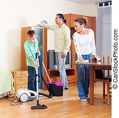 Parents and boy cleaning together in living room