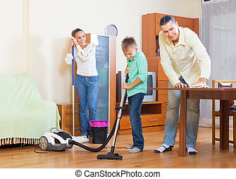 Couple with teenager dusting together - Middle-aged couple...