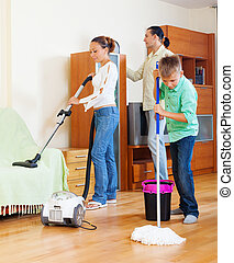 family with teenage boy cleaning in living room - family of...