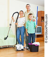 Family dusting with vacuum cleaner - Happy couple with...