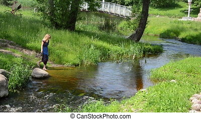 girl rocky stream - girl holds in the hands sandals and...