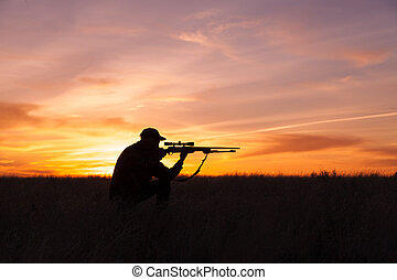Silhouetted Hunter - a rifle hunter silhouetted in a...