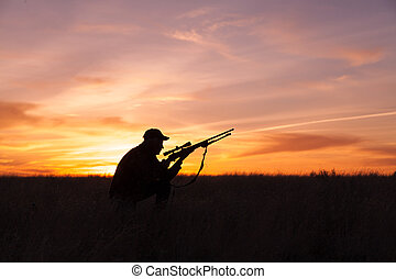 Silhouetted Hunter at Sunrise - a rifle hunter silhouetted...