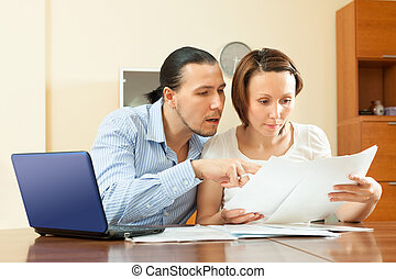 couple calculating family budget at home interior - couple...