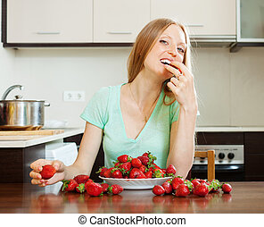 Blonde girl eating strawberry in home