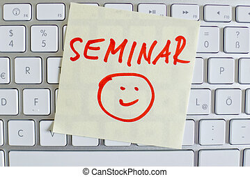 note on computer keyboard: seminar - a sticky note is on the...