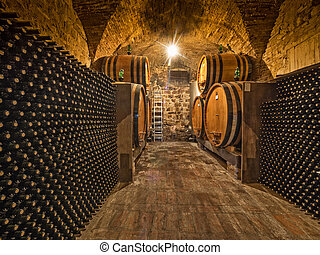 wine bottles and oak barrels - wine bottles and barrels in...