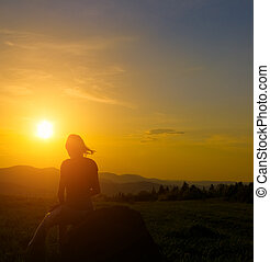Silhouette of woman in mountain at sunset