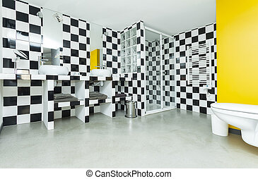 Modern bathroom with checkered black and white tiles on...