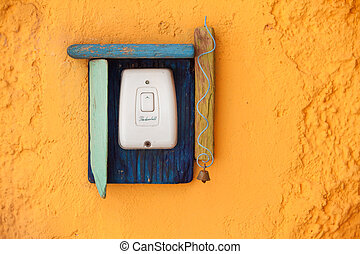 The doorbell button with wooden decoration on the old yellow...