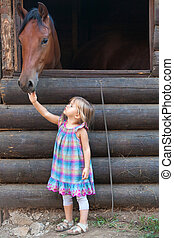 Little blond girl petting the brown horse