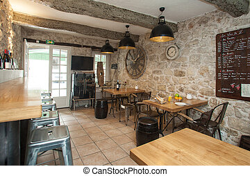 Interior of French bistro with rustic furniture.