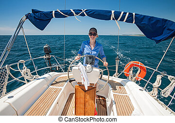 Young woman standing at the helm of a boat against a blue...