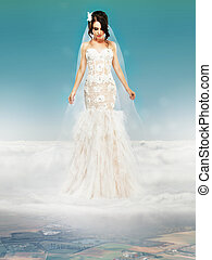 Bride in Wedding White Dress standing on a Cloud and Looking...