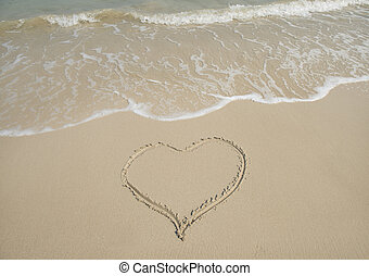handwritten heart on sand