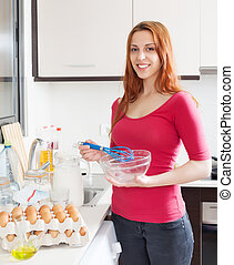 Smiling woman cooking omelet