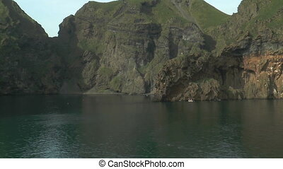 passing cliff coast at westman islands in iceland, view from...
