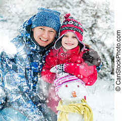 Family with a snowman - Father and daughter making a snowman