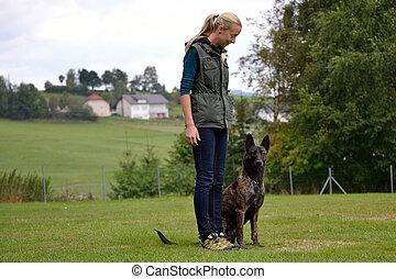 Junge Frau trainiert mit Hund - Hundeausbildnerin mit einem...