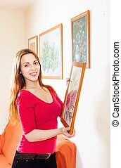 Long-haired girl in red hanging the  pictures